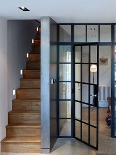 Internal steel-framed windows and doors act as a transparent screen between the living and eating spaces in the basement. A set of wood stairs with modern detailing leads up to the ground floor.