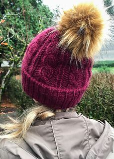 This easy cabled hat goes from basic to super sassy when you top it with a great big faux fur pom pom. Of course, a great big yarnie pom pom will do in a pinch!
