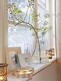 Candles on the window ledge. Branch as floral arrangement. Ethereal linen curtains.