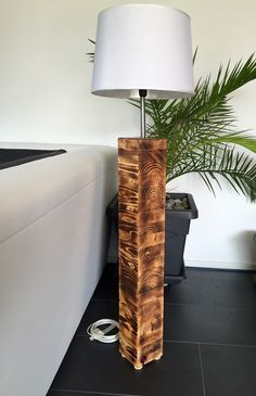 Stylish floor lamp, leg from kiln-dried and oiled Schichtverleimtem wood. Overall height approx. 1.20 m. White plastic screen. Eye-catcher in the entire room! These pieces are all unique and are made by us in Switzerland from Swiss wood. Like delivery we you this piece inside of