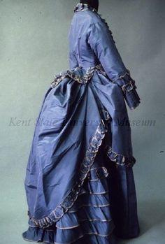 Ensemble Date1870-1879 CultureFrench DescriptionBlue silk taffeta. Bodice: center front buttons, peplum, silk trim. Skirt: vertical pleats at front, ruffles in back. Overskirt: bustle, ruffle trim.