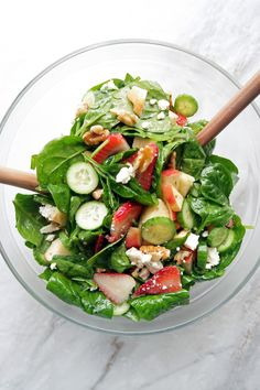 Summer Strawberry Cucumber Spinach Salad with Apple Cider Vinaigrette in a large glass bowl with two wooden spoons.