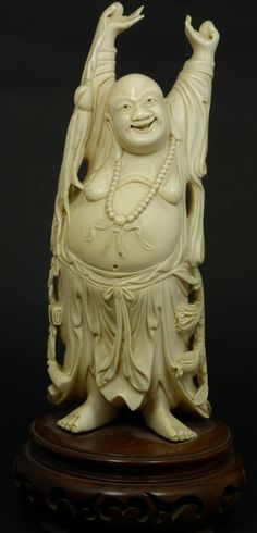 A Chinese hand carved ivory figure depicting a standing happy Buddha. He is wearing mandarin bead necklace and holding a tassel to right hand. Hanging from his belt is a pomegranate stalk and scroll to other hip. Mounted to round wooden base. Made Qing Dynasty period.