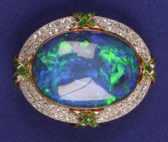 Opal, Diamond, and Demantoid Garnet Pendant/Brooch, c. 1910, centering an Australian peacock opal measuring approx 26.10 x 18.10 x 6.15mm, framed by two rows of bead-set single and old European-cut diamonds, approx. total wt. 0.80 cts, with calibre-cut demantoid garnets, platinum topped 14kt gold mount, removable brooch fittings.