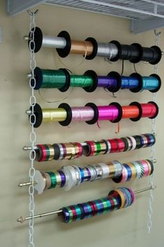 Clever, easy and inexpensive way to store ribbon or even gift wrap for easy access.  No carpentry required.  Just 2 equal lengths of chain.  Always adjustable depending on roll's thickness.  no leveling of hooks or boards!