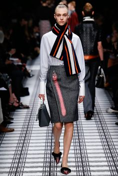 Balenciaga's Fall 2015 outfit is inspired by 1950s fashion. The fitted silhouette with A-line skirt at knee length resembles style lines of the decade. The high neck and scarf resemble airline stewardess fashion seen in the 40s and 50s. 3/ 18/ 15