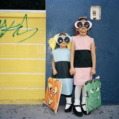 """Powerpuff Girls by Amy Stein.   Photographer, Amy Stein, documents a unique experience for children in Harlem, """"they don't go door-to-door asking their neighbors for treats. Instead, they walk up and down Lexington and 2nd Ave collecting candy from the many liquor marts, dollar stores, beauty shops and bodegas. It is a ritual that is at once completely familiar and yet wholly unique to this culturally vital and rapidly gentrifying area of Manhattan""""."""