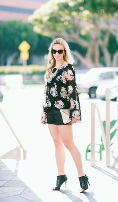 Juxtaposition: black floral flowy blouse, pastel statement necklace, black vegan leather shorts, gold clutch, black peep-toe booties