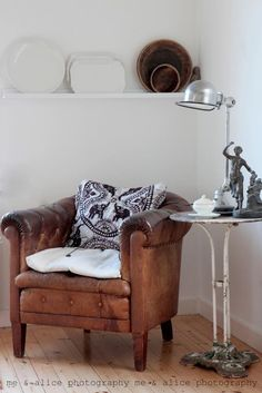 Brown leather chair with black and white cushion