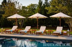 Four teak loungers encourage guests to get some sun by the cool pool. - Photo: John Bessler / Design: India Hicks