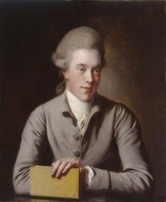 1777–1780.   Portrait of a Gentleman by Joseph Wright of Derby Portrait of young, eighteenth-century man, forward-facing with his head turned to the right. He is depicted wearing a wig with ringlets above the ears, a grey coat unbuttoned at the collar with a pink lining, shirt cuffs visible at the wrist, and a stock tied round his neck. The figure leans forward slightly to rest his folded arms on a surface in the lower foreground and places his left hand on top of a book.