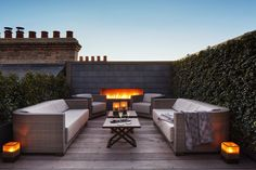 This rooftop combines a built-in fireplace, plant-covered walls, wood flooring, and comfortable outdoor furniture, to create a quiet escape from busy London life.