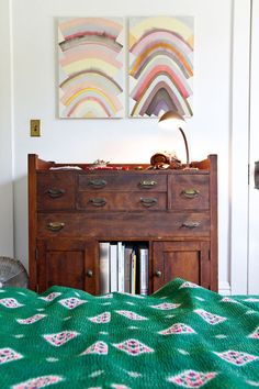 I love all three things in this photo: the blanket, the awesome dark/old dresser, the wall art.