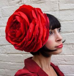 Giant bright red flower headpiece, handmade out of recycled fabrics in shades of bright pillar box red. Its held in place with a black covered alice band