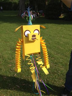 adventure time JAKE THE DOG 1st birthday piñata. Made with recycled cereal and soap boxes. And covered in yellow carboard. With bouncing arms and legs.