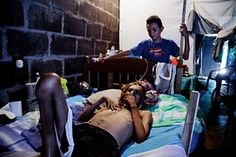 Former sugar cane worker Don Julio Lopez lies in a hospital bed with his son watching over him Helping Others, Helping People, Heat Stress, Hospital Bed, Chronic Kidney Disease, Sugar, America, Life, El Salvador