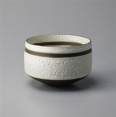Lucie Rie: Straight-sided bowl, Porcelain and stoneware mixed, white pitted glaze with unglazed band, foot and lip. 6 5/8 in. (16.8 cm.) diameter, c.1977