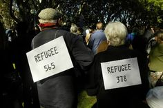 Two people wear signs on their back to protest the treatment of refugees. Photo: Dean Sewell