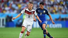 Toni Kroos of Germany (18) and Enzo Perez of Argentina (8) compete.