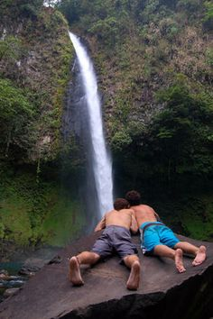 Couple of men laying on rock and viewing waterfall near city of Arenal, Costa Rica. Can visit volcano and hot springs from here