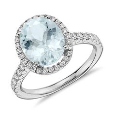 A vision of cool oceanic color, this aquamarine and diamond ring features an oval aquamarine framed by a halo of forty-four pavé-set round brilliant diamonds in 18k white gold.