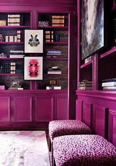 I love the dedication to color. Magenta colored built-in shelving in a library with styled, wallpaper-backed bookshelves