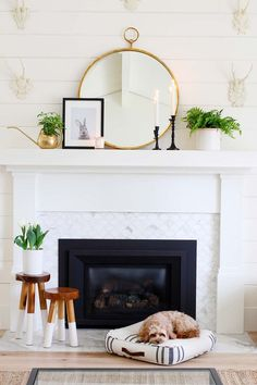 a modern spring mantel with a round mirror, greenery in a pot and a watering can, candles and a bunny print in a frame Simple Fireplace, Farmhouse Fireplace, Fireplace Design, Farmhouse Decor, White Fireplace Mantels, Modern Farmhouse, Fireplace Ideas, Farmhouse Ideas, Decorating Fireplace Mantels