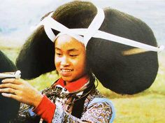 Miao women,living in Zhijin of Guizhou Province,dress their hair up with black knitting wool to form a supper large coiffure.