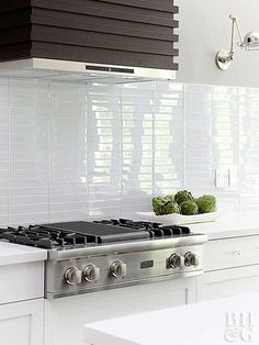The pattern that forms when tile is installed can communicate a style statement as effectively as the tiles themselves. In this clean, contemporary space, 2x10-inch white glass backsplash tiles stack up in arrow-straight columns rather than in a traditional running bond pattern. The kitchen backsplash underscores the emphasis on parallel lines found throughout, including the range hood made of stacked ribs of riftsawn wood.
