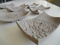 These are slabs of white clay, we added texture with doilies, pressing them on the clay slab, then we put the slab in a small dish to give it the curved shape (it's possible also to dry it with a h…
