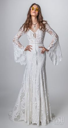 """Rish Bridal 2018 """"Sun Dance"""" Collection – Romantic Bohemian Rustic Chic Wedding Dress. ALMA, a romantic bohemian sheath bridal gown with bell sleeves and bow tie at the V-neckline. The bodice and skirt are made from a crochet lace delicately beaded with Swarovski gems for a touch of glam. #RishBridal #SunDance #AlmaByRish #Sponsor #BohoBride #BohoChic #BohoGown #Wedding #WeddingDress #Bridal #WeddingGown #Bride #Romantic #WeddingDresses"""