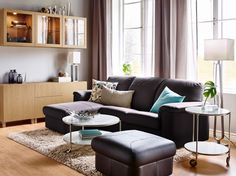 A living room with a dark brown two-seat leather sofa with chaise longue and a footstool. Combined with a round coffee table and storage in oak effect.