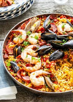 Thinking about Christmas Eve dinner! This saffron-infused Seafood Paella is loaded with mussels, clams, and shrimp. Cook it on the grill for best flavor. It serves a crowd and would be so much fun for your next cookout! Seafood Recipes, Dinner Recipes, Cooking Recipes, Healthy Recipes, Seafood Paella Recipe, Grilled Paella Recipe, Best Paella Recipe, Paella Food, Spanish Paella Recipe