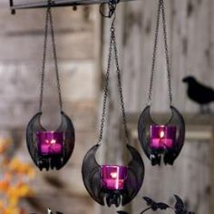 """Hanging Bat Votive Holder  Metal mesh wings unfurl mysteriously around a 4 3/4""""h purple glass cup for use with a votive or tealight, sold separately. Remove chain for tabletop use. Overall: 14 1/2""""h, 5""""w."""