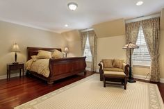 This sleigh style bed coordinates perfectly with the cherry-tone hardwood flooring.  A comfortable armchair keeps with the same theme, with it's carefully curled arms and curved lines.  A simple patterned light sage and cream area rug highlights the same light sage on the walls, while patterned linens, drapery, and throw pillows contribute additional interest to the room.