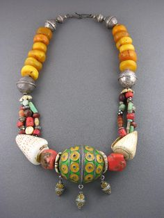 by Anne Holland | Enameled centerpiece with antique silver beads and Mediterranean coral; antique carved conus shells and discs; ancient amazonite; antique and ancient shells; antique silver, carnelian, and trade beads; and antique Tibetan amber. | Dorje Designs