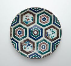 Dish  1644-1650      Edo period     Porcelain with cobalt pigment under transparent glaze and enamels over glaze  H: 7.0 W: 35.0 cm   Arita, Japan.   Within an overall geometric grid, smaller geometric patterns fill concentric bands of contrasting colors. Three six-sided bands frame bird-and-flower motifs inspired by Chinese painting.