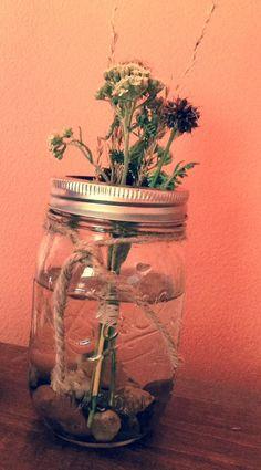 Ball jar with wildflowers and rocks.
