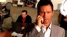 """Stop…we got a burn notice on you. You're blacklisted."" [male voice on the other end.of the phone call]  ""Excuse me."" [Michael Westen]  Pictured: Michael Westen (Jeffrey Donovan), Boris (Dimitri Diatchenko, seated), male voice (Matt Nix)"