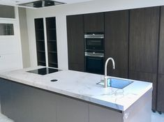 Kookeiland in mat lak met Decton werkblad, hoge kastenwand in Noten hout met inbouw apparatuur van Siemens