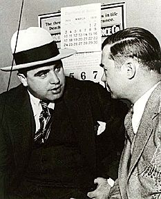 Jazz Title: Al Capone and attorney Year: 1929 This is a picture of the famous American Gangster, and fashion icon to boys, Al Capone. Here he is shown wearing a fedora. His shirt is a stiff Barrymore collar, long and pointed at the end. He is wearing a necktie as well.