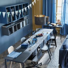 3 tables are arranged lengthwise for a dinner party, while a fourth table serves as a buffet table.