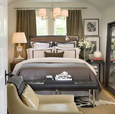 David Jimenez (after). Sophisticated brown & gray bedroom design with taupe brown velvet drapes, black beveled floor mirror, black leather tufted bench, cowhide rug, gray bedding duvet and sisal rug.