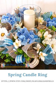 Spring Candle Ring -This beautiful hydrangea arrangement was made on a 18 inch evergreen base with burlap mesh and metallic blue mesh. The wreath is adorned with blue hydrangeas, white gerber daisies and pale yellow ginger flowers.