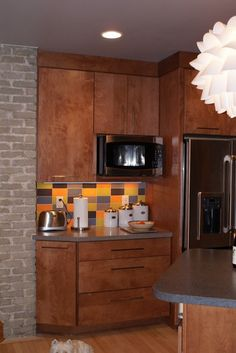 Exposed Cream City brick and a funky pendant light are a nod to the home's history. New standard base cabinetry was deconstructed and customized to angle back towards the chimney in order to expose the existing brick column and allow for better traffic flow.