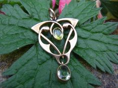 An absolutely stunning and eye-catching genuine fully hallmarked 9ct gold English Art Nouveau pendant, set with two lovely green peridots -