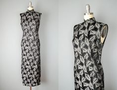 Gorgeous traditional Cheongsam gown is silver and black lamé woven in a feather motif. It features a mandarin collar and snaps that start at