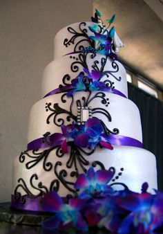 Fondant wedding cake with purple satin ribbon, black piped scrolls and fresh orchids.