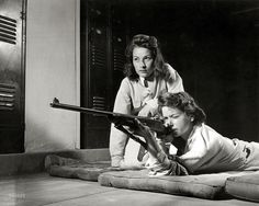 In a public school - August 1942. Training in marksmanship helps girls at Roosevelt High School in Los Angeles develop into responsible women. Part of Victory Corps activities there, rifle practice encourages girls to be accurate in handling firearms. Practicing on the rifle range in the schools basement.