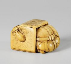 An ivory netsuke of an oni in a portable heater. Early 19th century